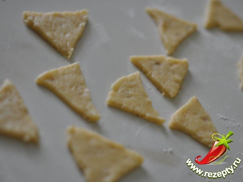 Раскатать тесто толщиной 3-5 мм, вырезать треугольники сторонами 6 см